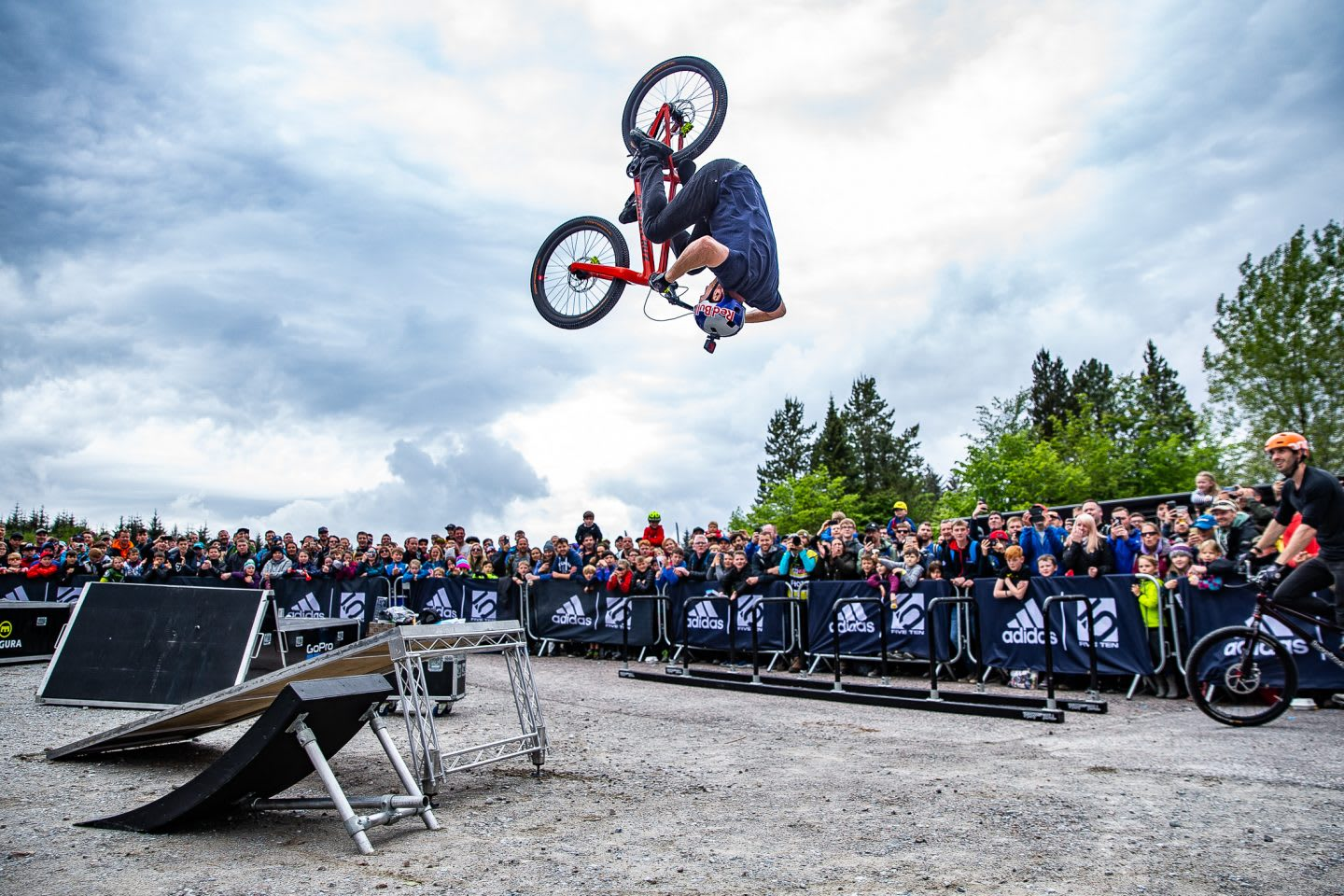 Mountainbike pro Danny MacAsill is doing a flip in front of a big crowd