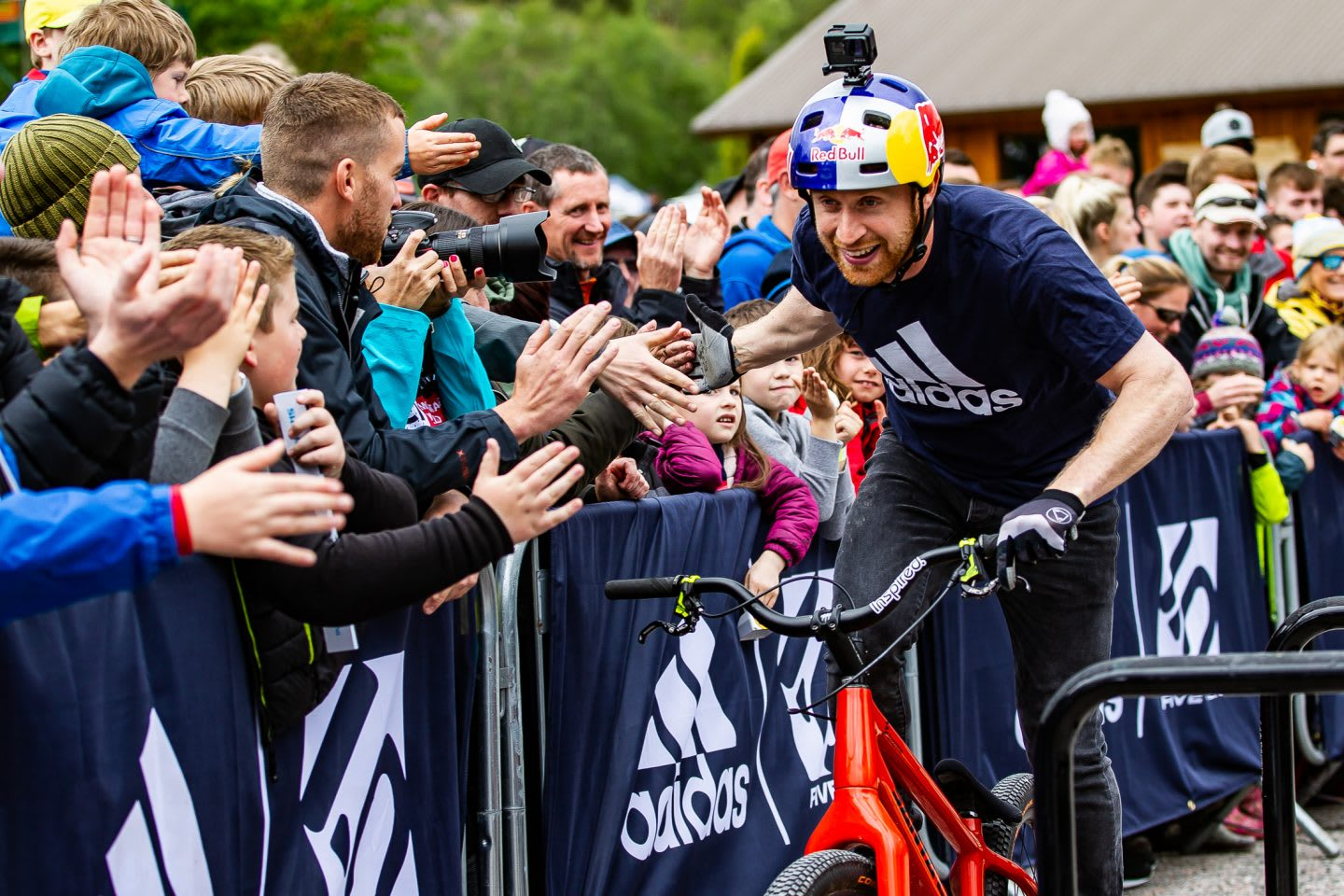 Mountainbike pro Danny MacAskill is giving his fans a high five while he passes them on his bike