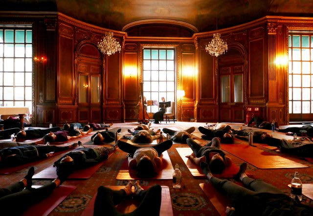 People do yoga on mats in a historic music chamber accompanied by live classical music. Wellness, Gameplan A.