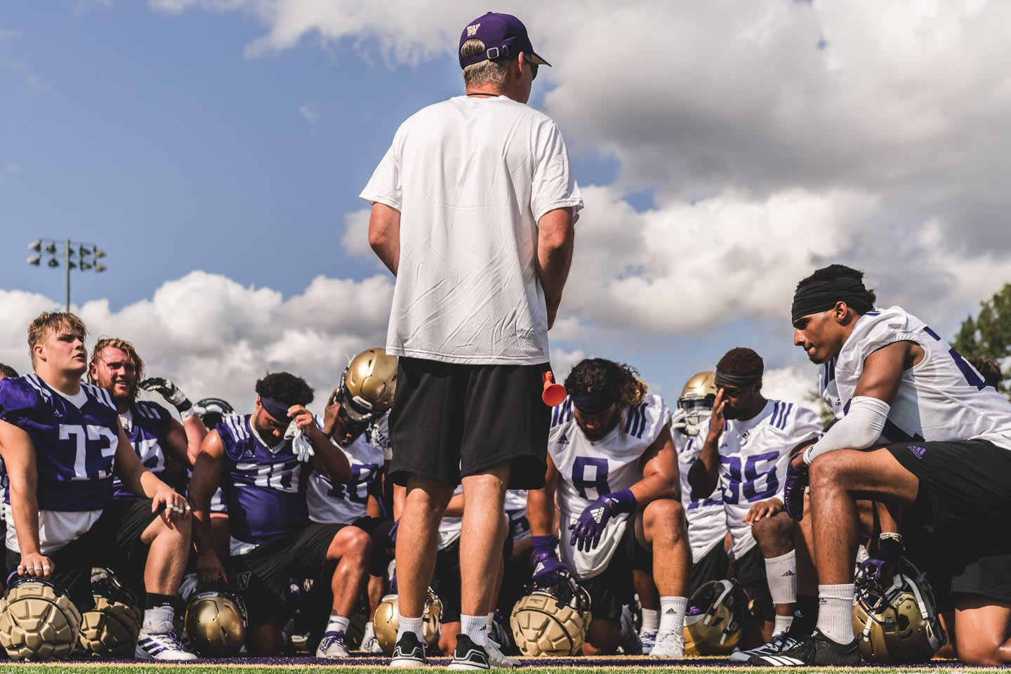 coach talking to his team of american football players