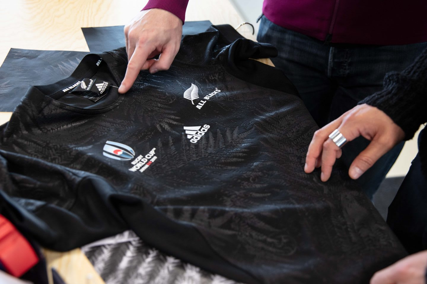 two hands touching a rugby jersey, all blacks jersey, all blacks, rugby, adidas
