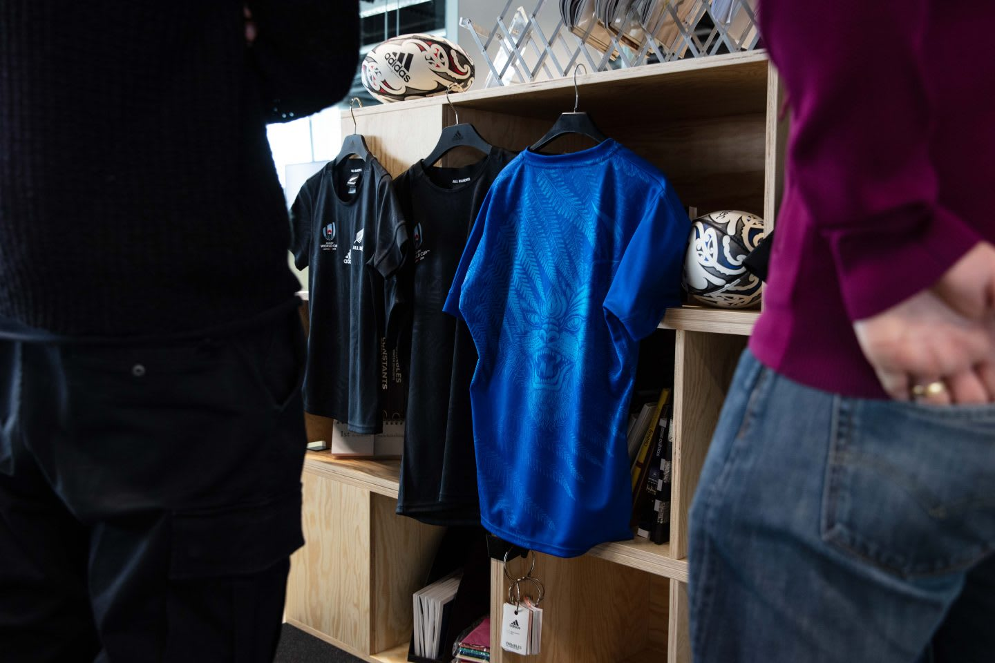three jerseys hanging from a shelf, all blacks jersey, all blacks, rugby, adidas
