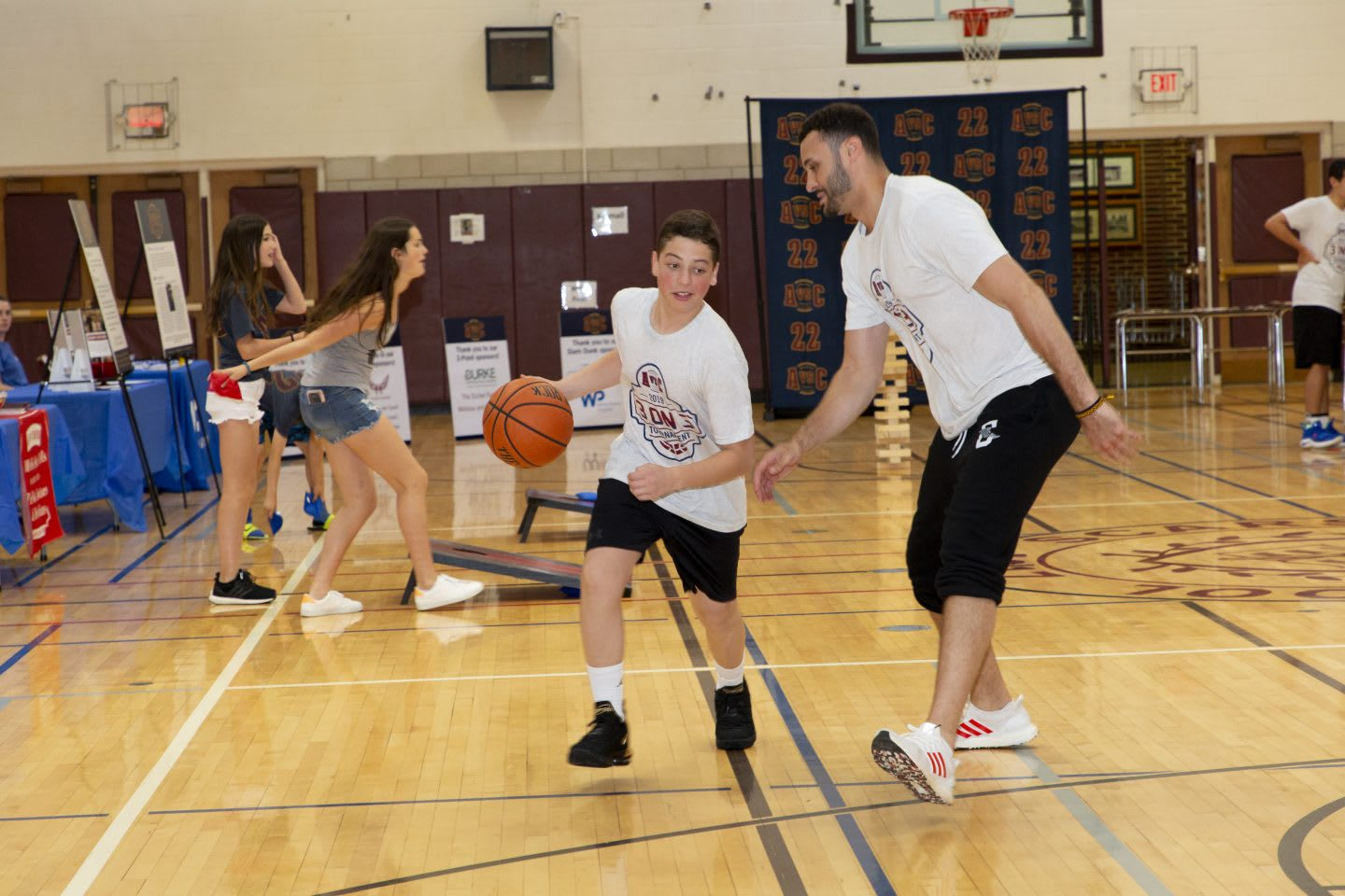 Larry Nance Jr. playing basketball with school children in a gym.