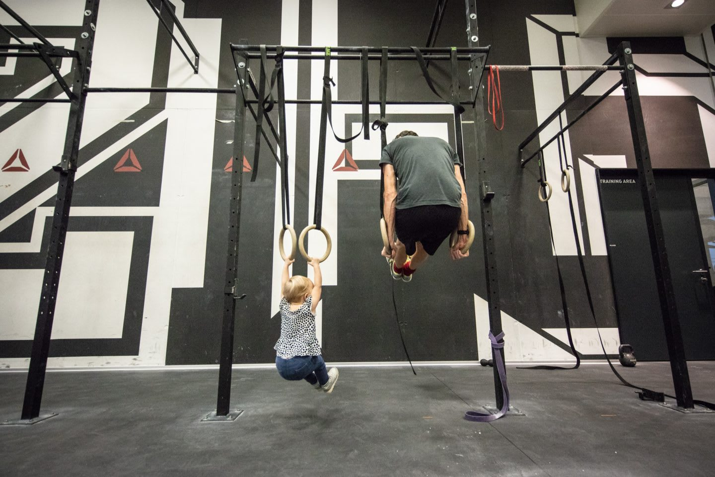 man working out with child in a crossfit gym