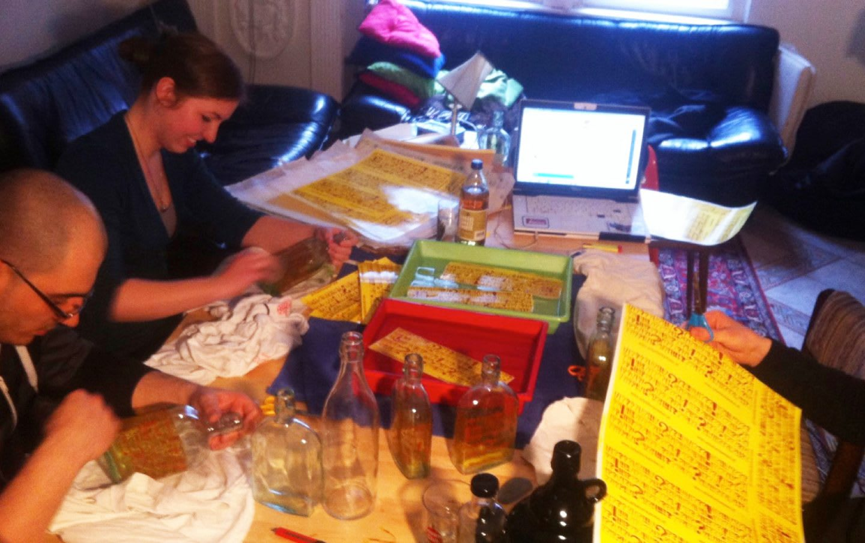 The soulbottle team decorating glass bottles in a living room.