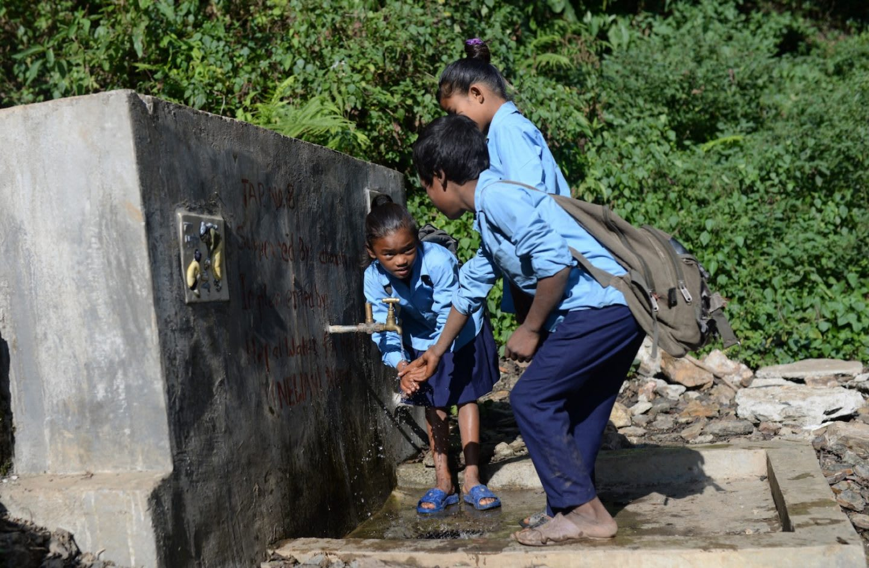 Children washing their hands in a water fountain.