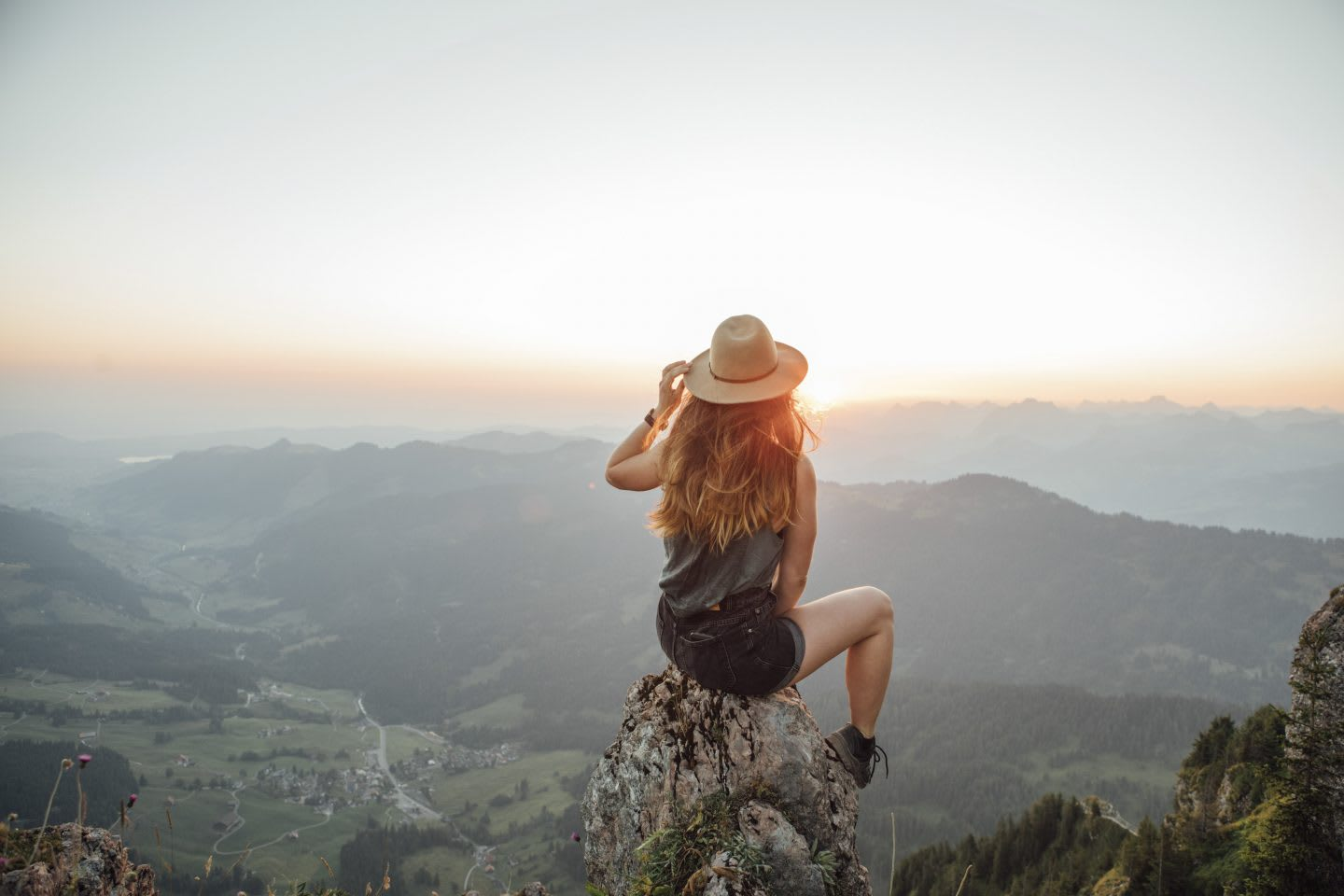 Woman sitting on a rock looking at the landscape in front of her. habits and routines, improving productivity, healthy lifestyle, rest and recovery, GamePlan A