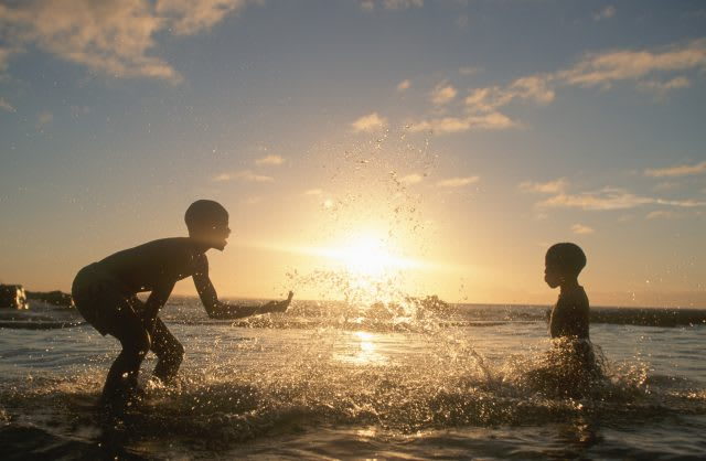 children playing together in the ocean, volunteering