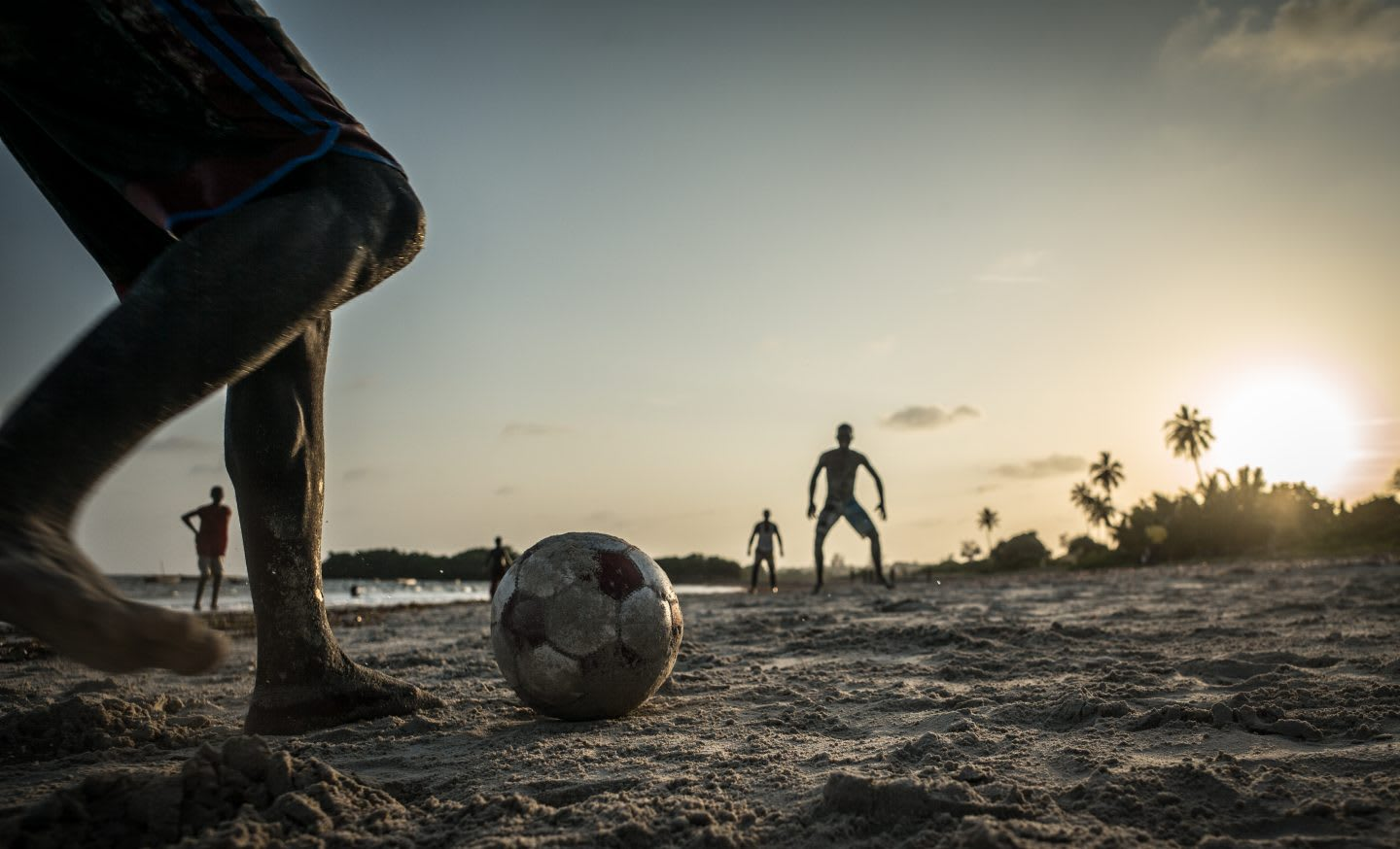 men playing football on a beach, volunteering
