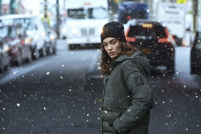 women standing in a street wearing an adidas coat whilst it is snowing