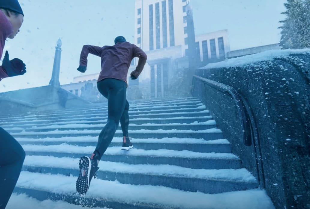 person running up stairs covered with snow, holiday season