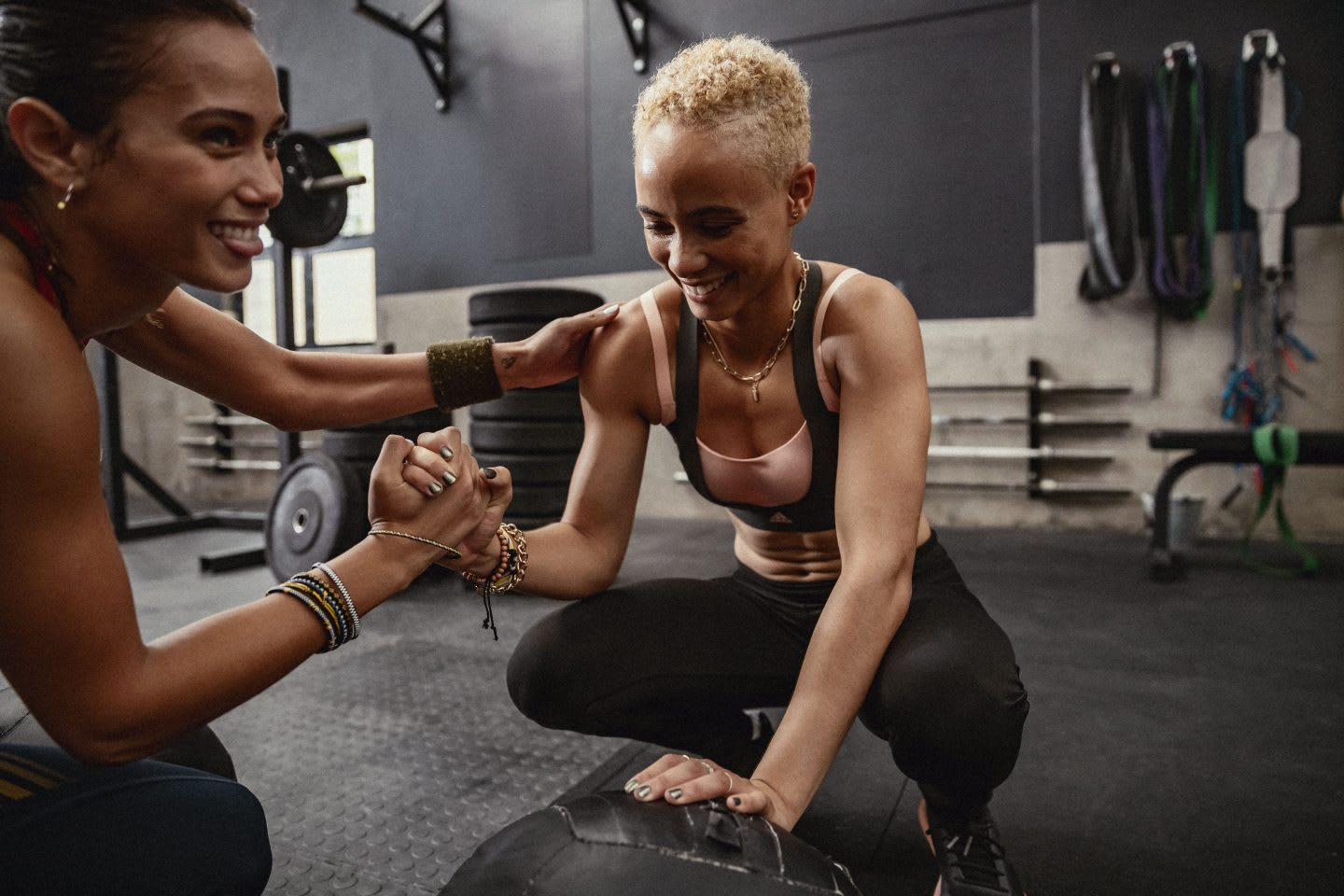 Woman lends support to friend while training in a gym.