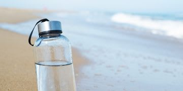 Closeup of a glass reusable water bottle on the seashore of a lonely beach. avoid plastic, sustainability, habits and routines, inspiration, GamePlan A.