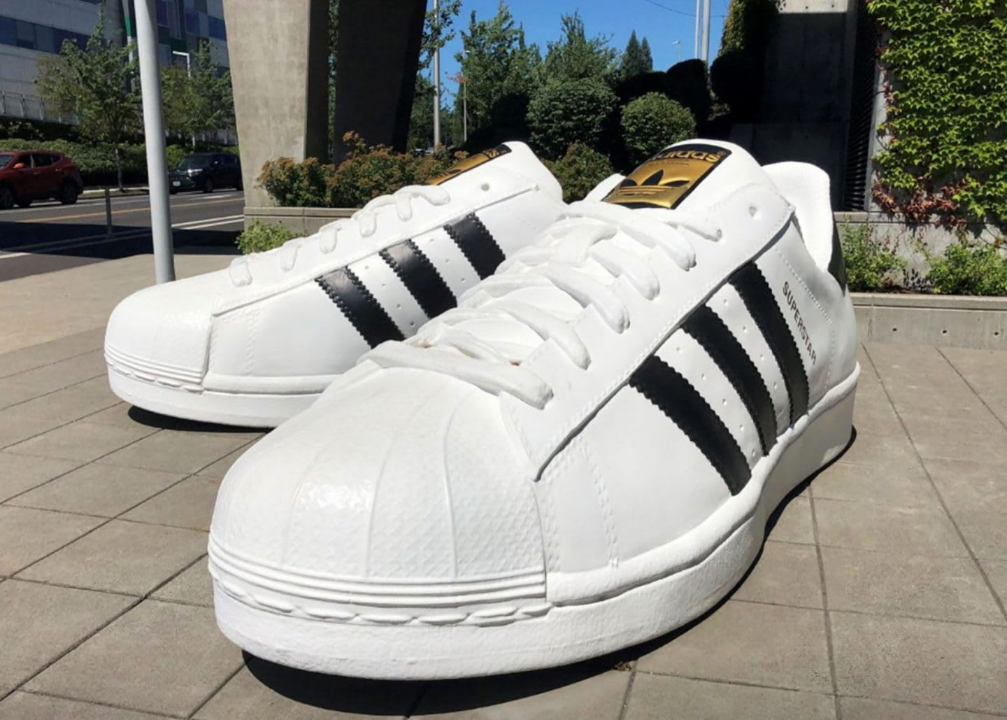 A pair of giant adidas Superstar sneakers standing on the ground in front of the adidas offices in Portland, GamePlan A