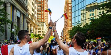 Two men wearing white vests wave tiny rainbow flags at a Pride event. Finding your purpose in life, Purpose meaning, Purpose Definition, Define Purpose, GamePlan A