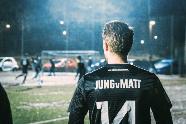Back of a soccer player with a JvM jersey on a soccer field . How to build a creative workplace culture, JvM, workplace, collaboration, creativity, team-building, GamePlan A