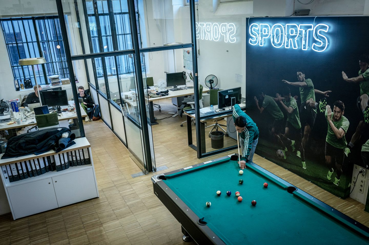 JvM office with a man playing billard. How to build a creative workplace culture, JvM, workplace, collaboration, creativity, team-building, GamePlan A