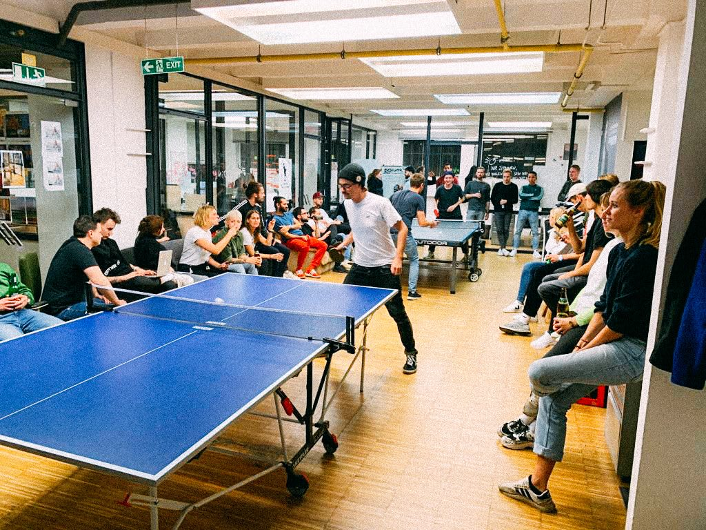 Group of people sitting in a room, some are playing table tennis. How to build a creative workplace culture, JvM, workplace, collaboration, creativity, team-building, GamePlan A