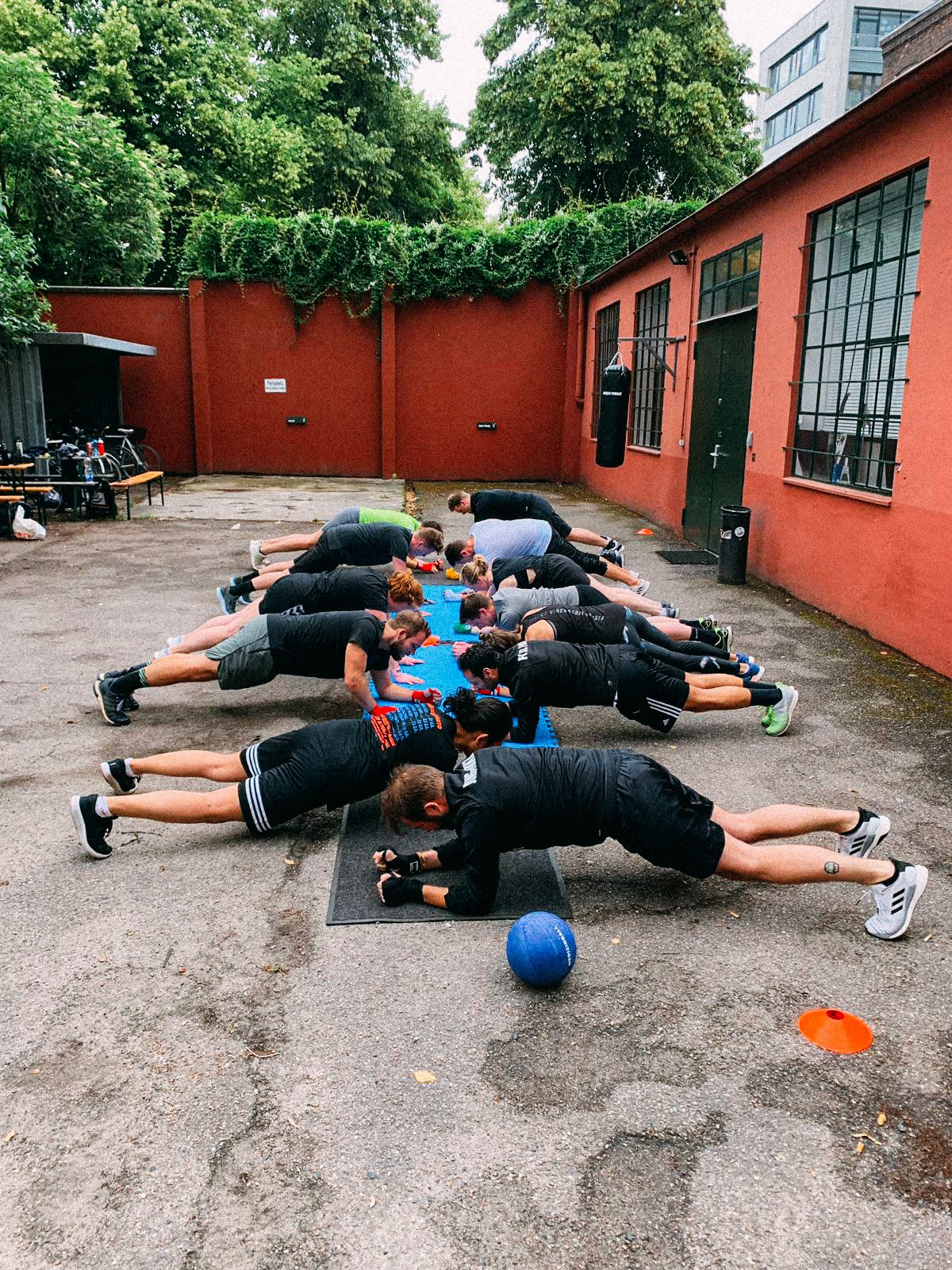 Group of people doing sports by doing planks on the floor. How to build a creative workplace culture, JvM, workplace, collaboration, creativity, team-building, GamePlan A