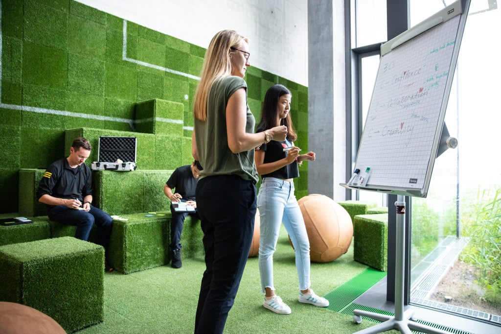 People in an adidas meeting room, two of them brainstomring in front of a flipboard. career choices, working in adidas, adidas recruitment, career development, GamePlan A