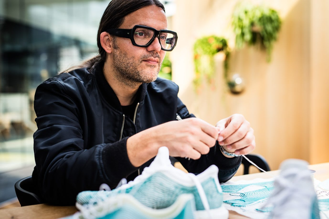 A man wearing big glasses sitting at a table with shoes and material made from ocean plastic in front of him. Finding your purpose in life, Purpose meaning, Purpose Definition, Define Purpose, GamePlan A