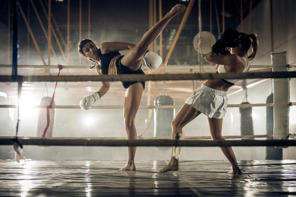 two women in kickbox training in the ring