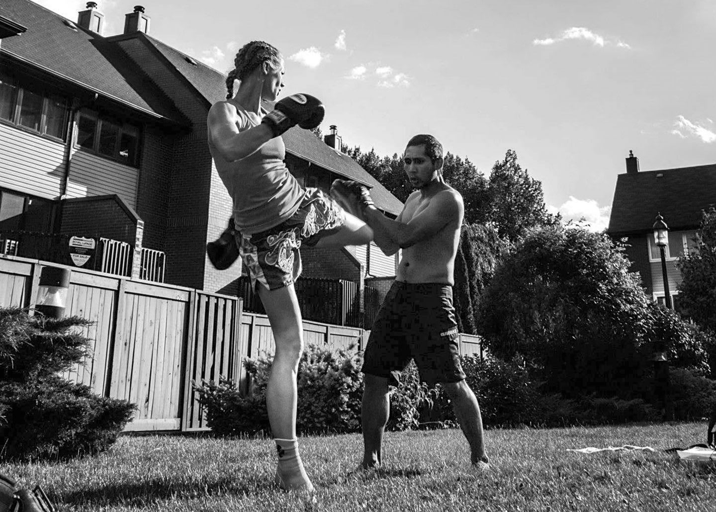 a women and a man kickboxing in a backyard