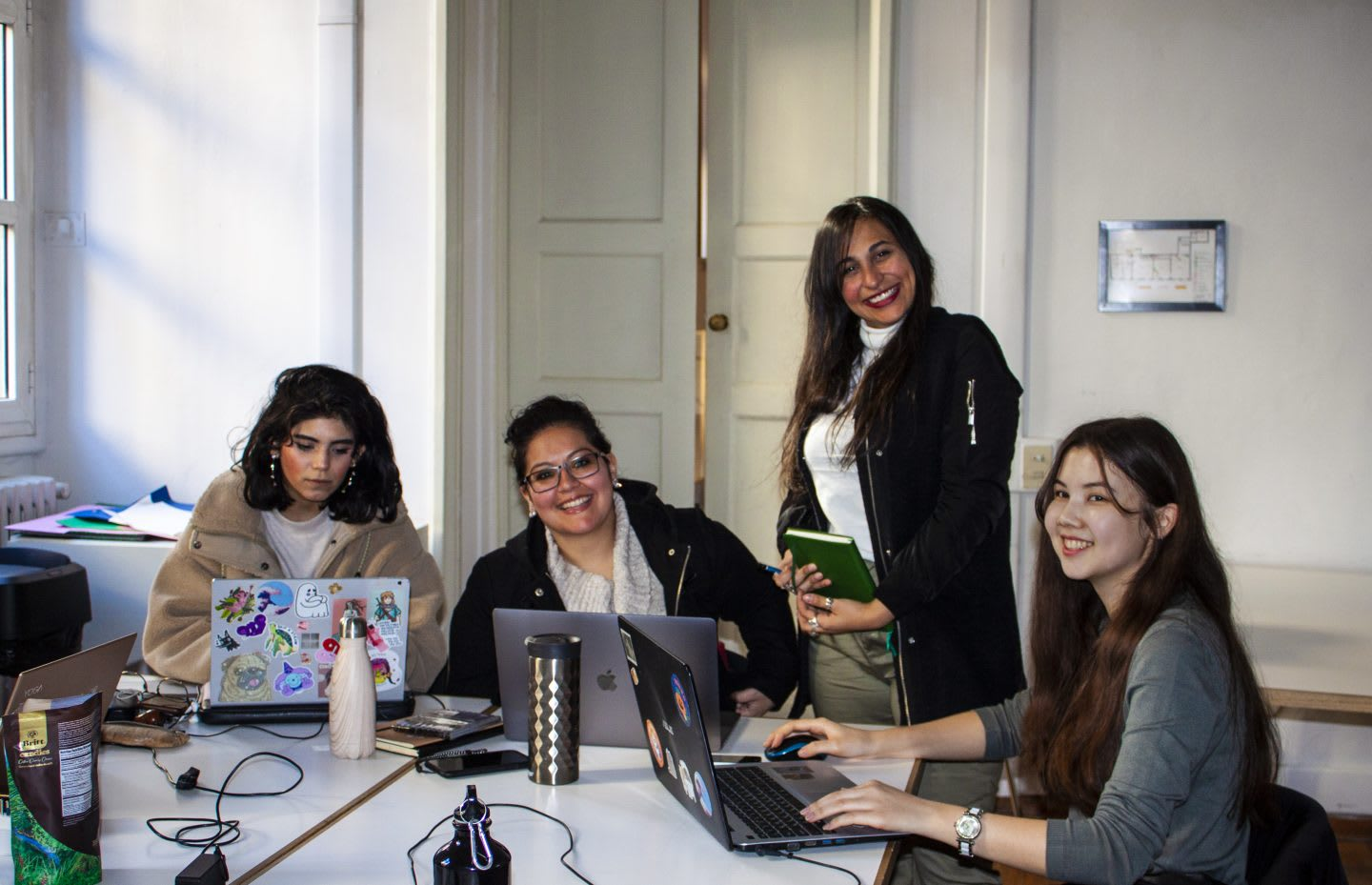 a team of female employees sitting at a desk working, playing as a team