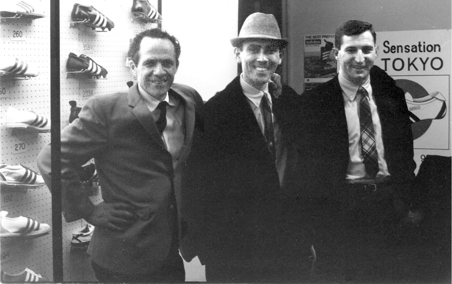 Black and white phtot of Horst Dassler with brothers Clifford and Chris Severn at the 1965 National Sporting Goods Association show in Chicago.