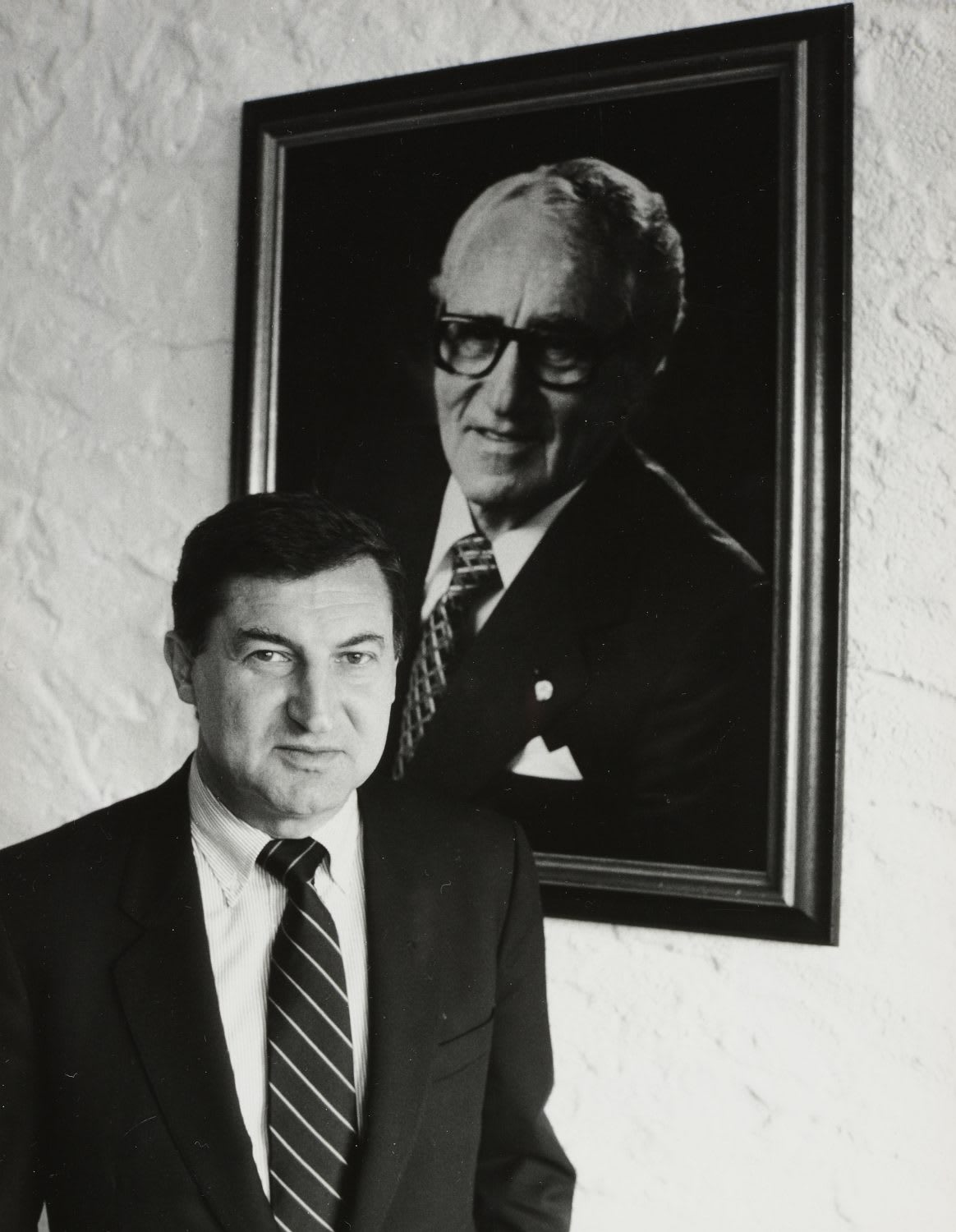 Black and white image of Horst Dassler standing in front of a portrait of his father Adi.