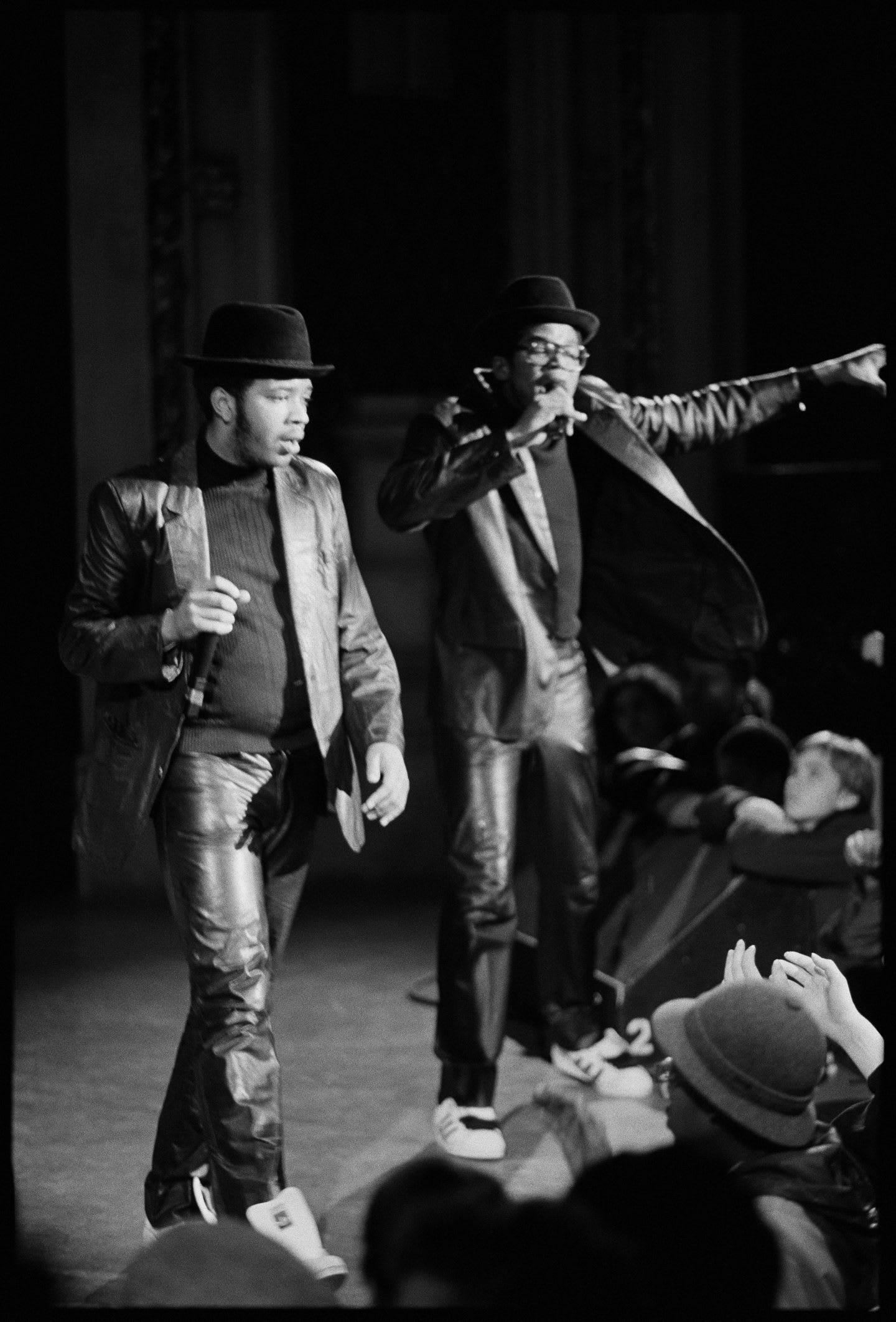 Run DMC perform on stage wearing their superstars. The image is black and white and the performers are facing the crowd with arms in the air.