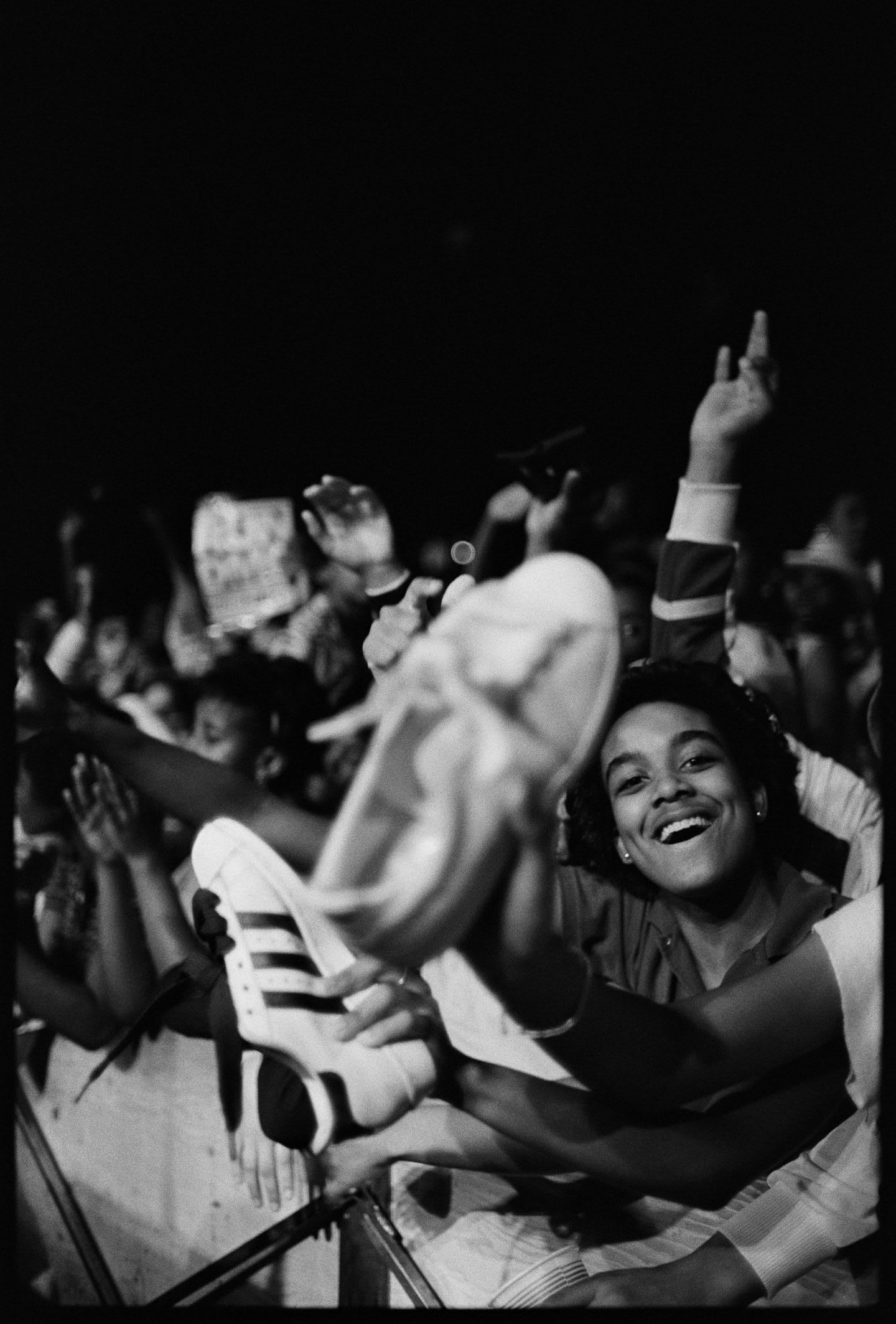 Fans at a Run DMC concert watch the show with their hands in the air and holding up their adidas Superstars.