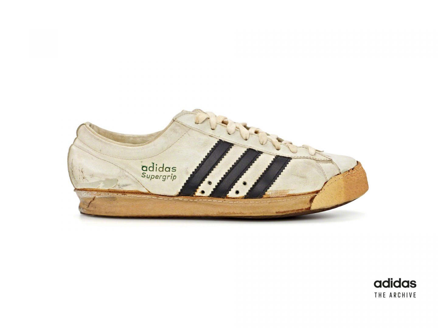 Image of supergrip shoe which is a white leather shoe with three black stripes on the side of the shoe.