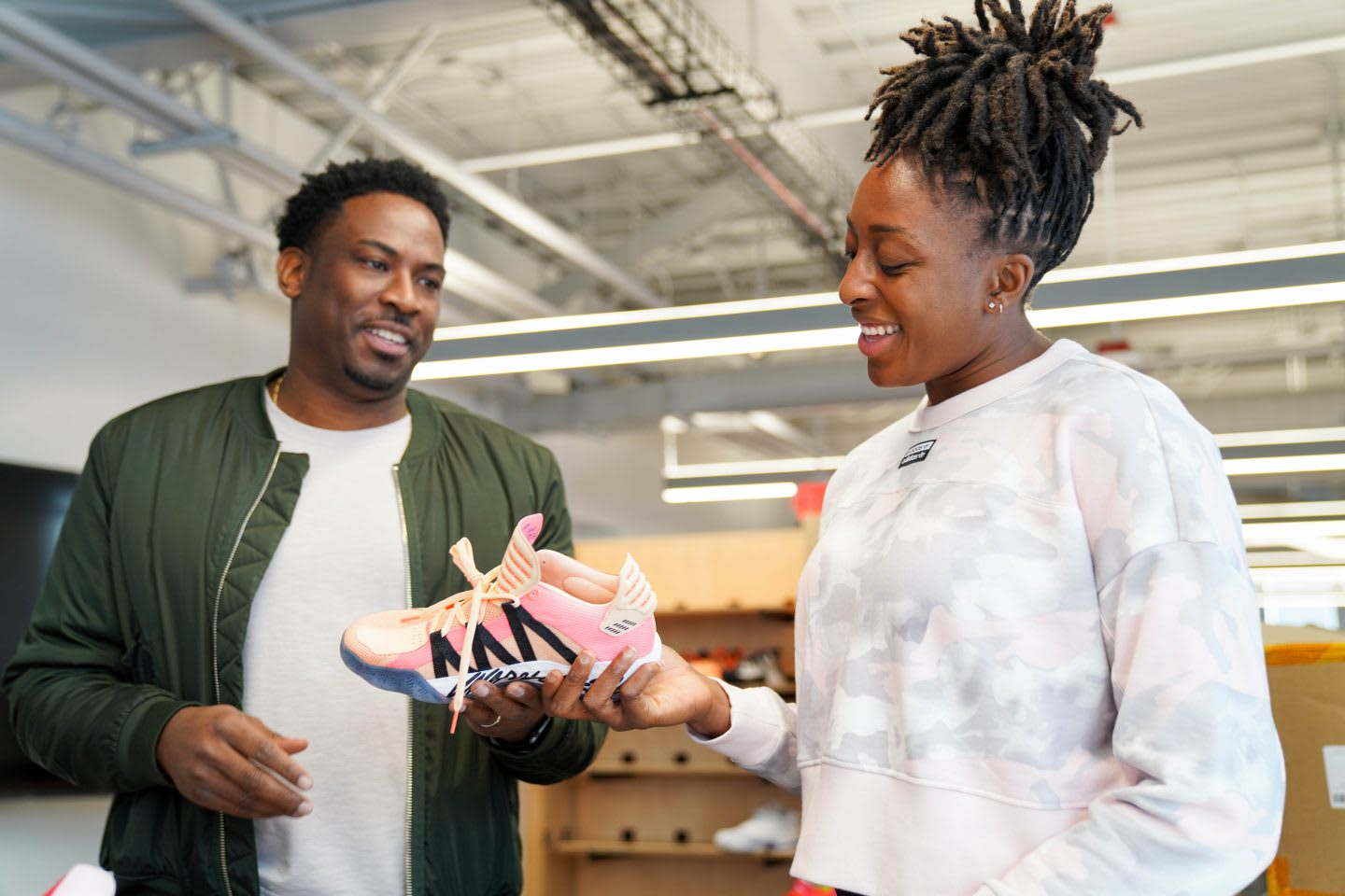 WNBA player Nneka Ogwumike holding sneaker and talking to colleague in the office, creativity, sports, work, collaboration, teamwork, teammates, GamePlan A
