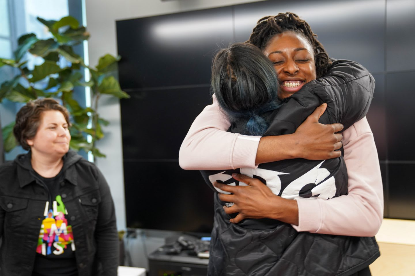 WNBA player Nneka Ogwumike hugs colleague while smiling happily, teamwork, friendship, collaboration, happy, appreciation, GamePlan A