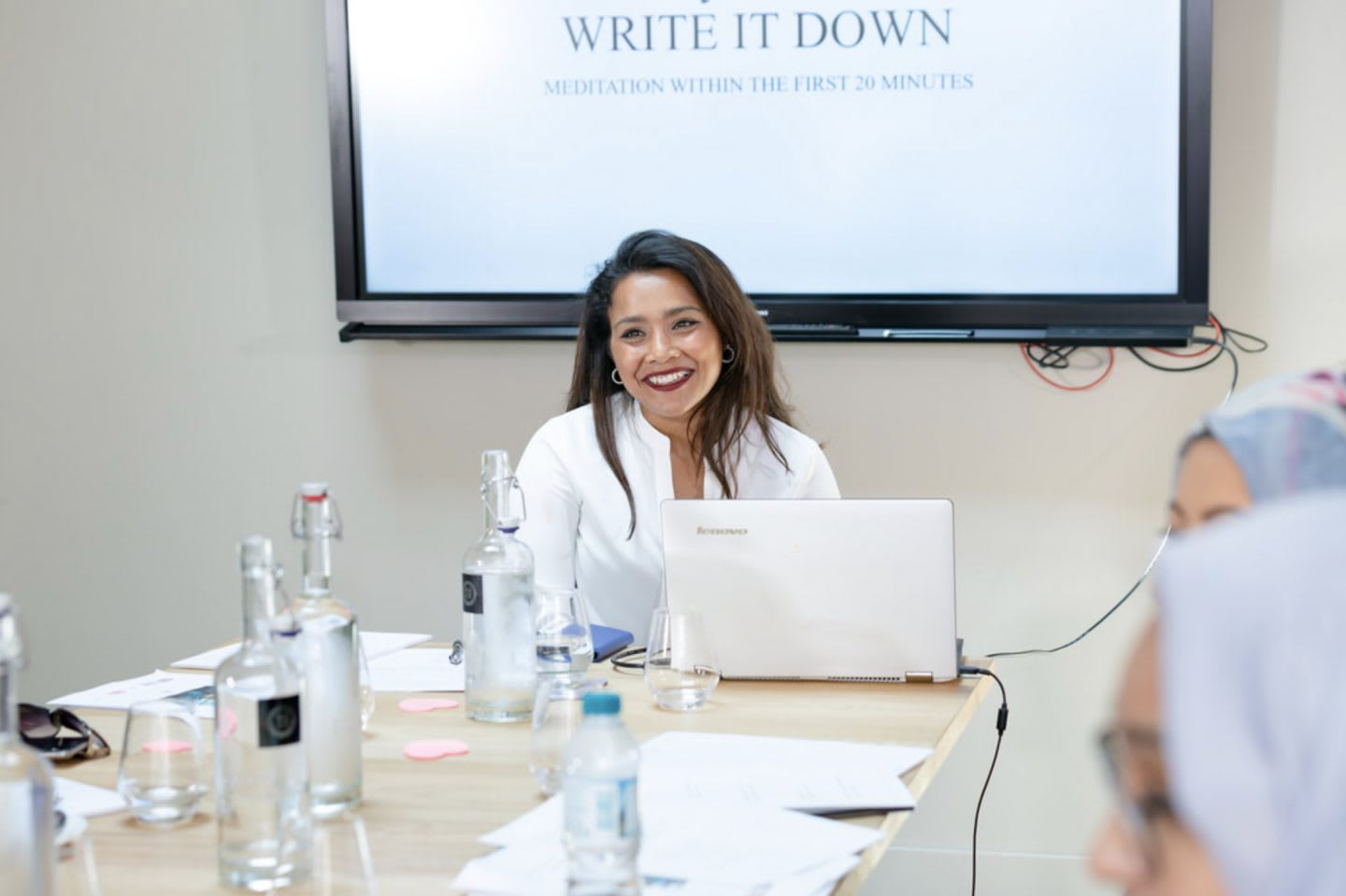 A women presenting in front of a screen to a group of women. Experience with depression, nazia, women, business, coaching, work, mental strength, mindfulness, GamePlanA