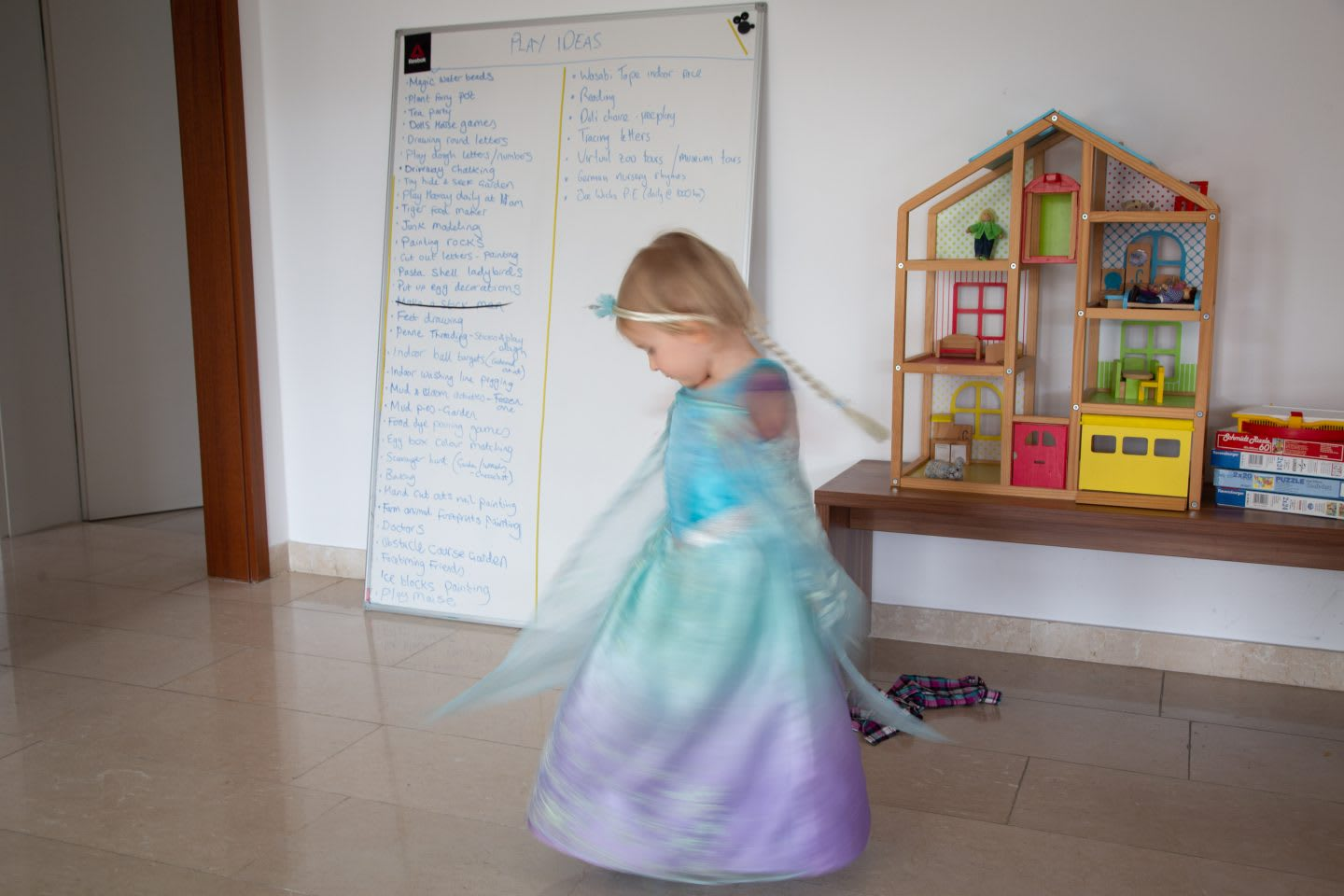 Girl dancing at home in princess costume and a whiteboard that shows a list of play ideas in background. working from home with kids. Habits and routines, Parenting, coronavirus.