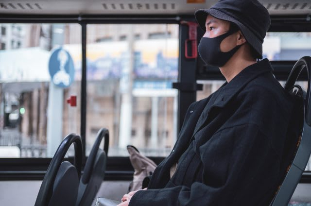 Young Asian man with protective face mask on public transport, bus, health, safety, coronavirus