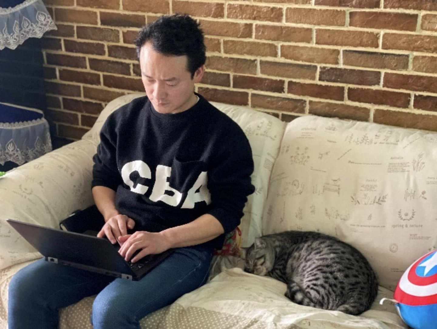 Man working from home on laptop next to pet cat, work from home, remote working, home office, China, Wuhan, coronavirus