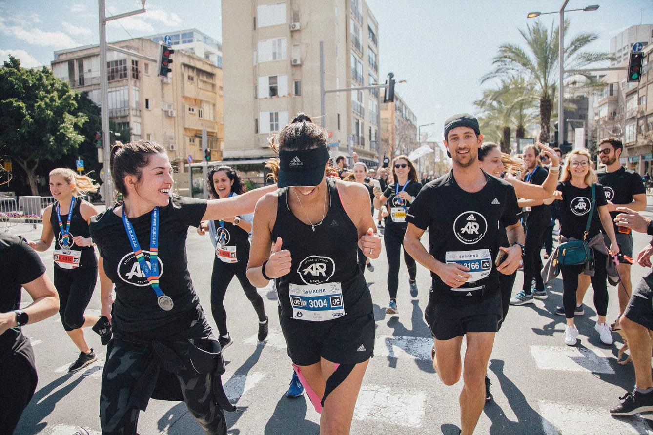 A group of adidas Runners running through the streets and celebrating.