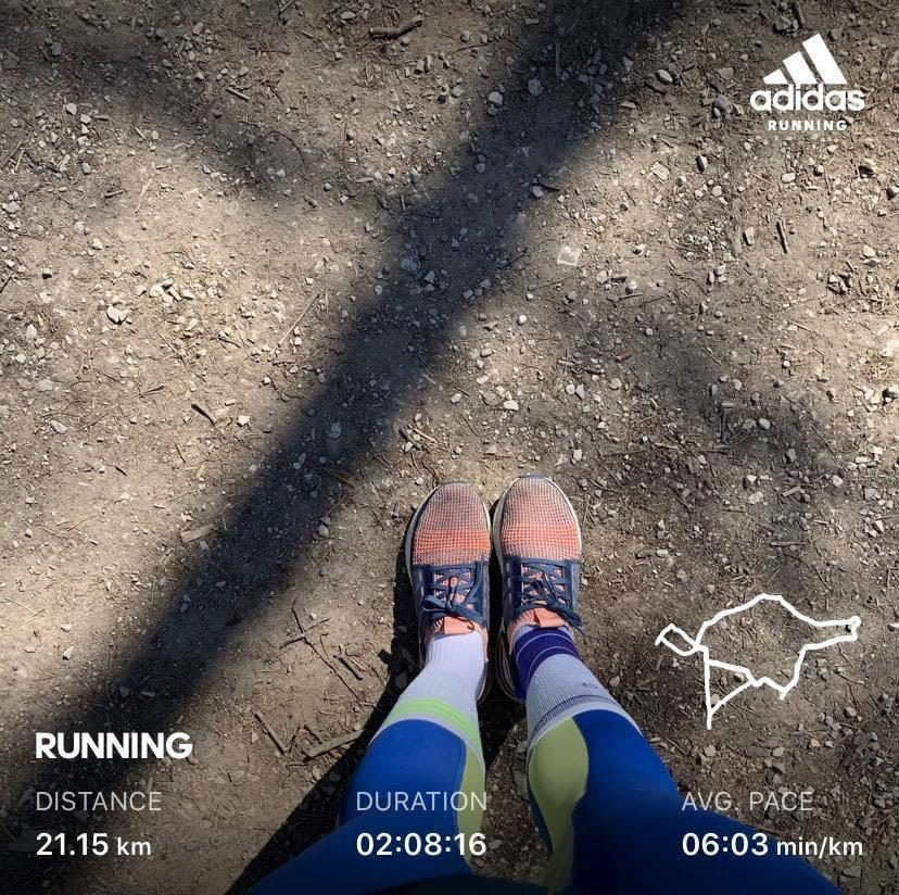 A women showing her running progress within the adidas Running app and her running shoes. Running communities, running, runtastic, athlete mindset, collaboration, motivating the team, GamePlanA.
