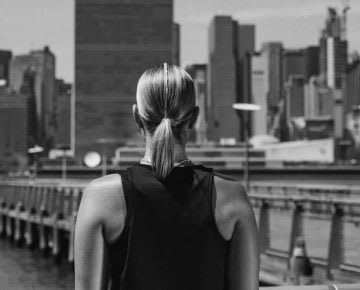 A women standing next to a pier looking on the skyline of a city on the opposite site of the river.