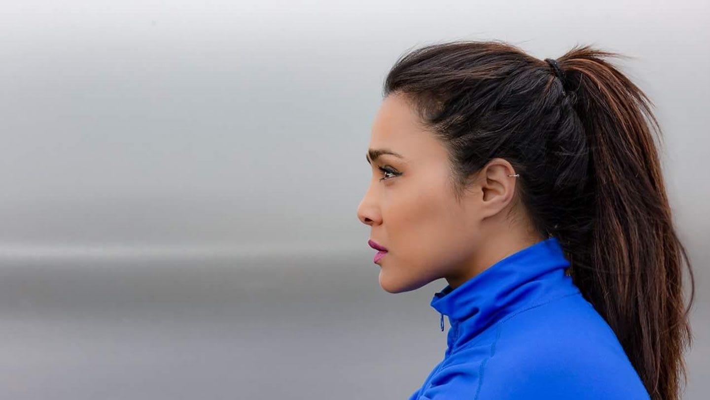 A women looking focused into the horizon wearing a blue training jacket.