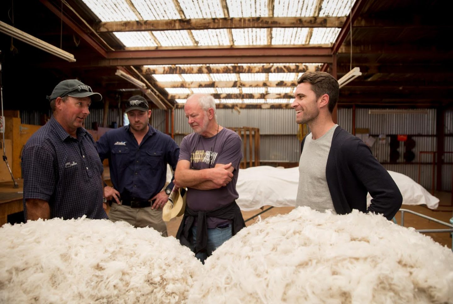 Men talking in a wool factory and smiling, Tim Brown, CEO, Allbirds, sustainability, sustainable, eco-friendly, wool, material, New Zealand