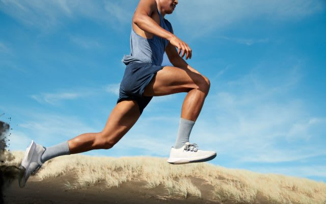 Man wearing sports clothes jumping in the sand, Allbirds, shoes, trainers, sneakers, running, sports, exercise, sustainability, eco-friendly, sustainable