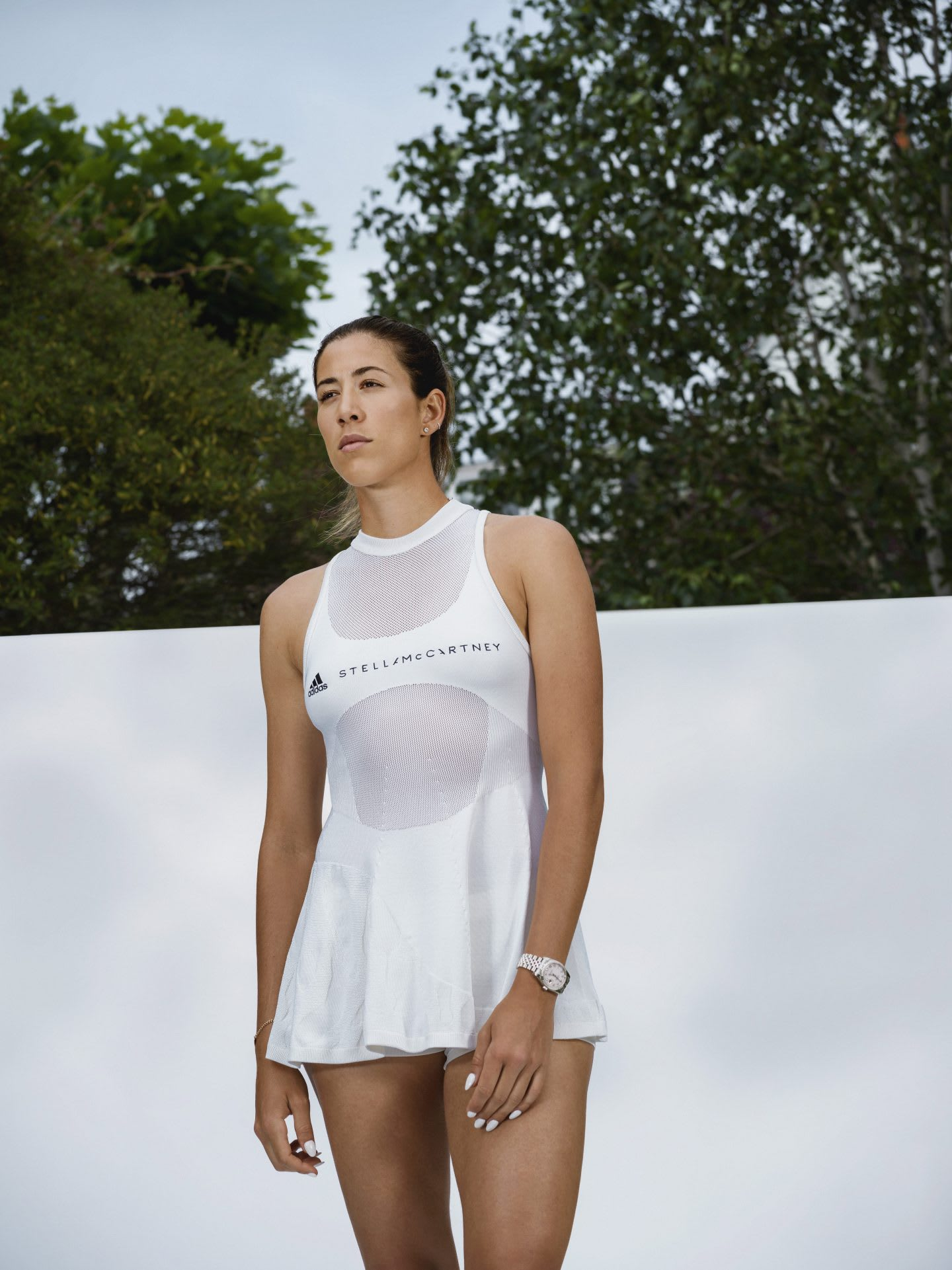 A woman wearing a white tennis dress by adidas Stella McCartney. plastic waste, Stella McCartney, adidas, bionic tennis dress, sustainability