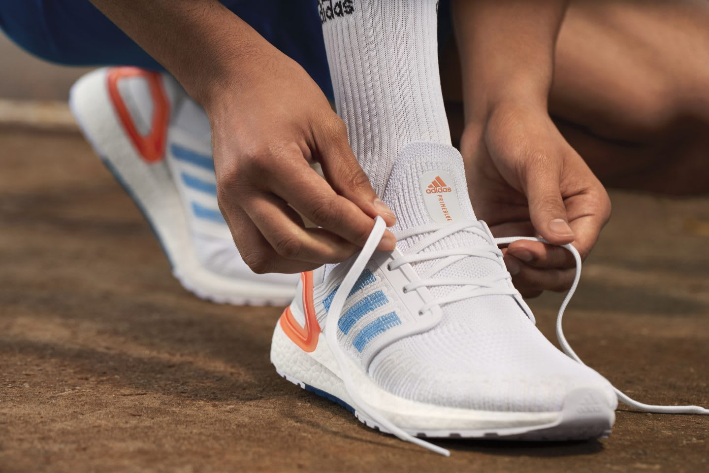 A person lacing up white adidas running shoes. plastic waste, adidas, Primeblue, sustainability, GamePlan A
