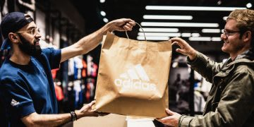 Sales person wearing hat handing over shopping bag to smiling customer, adidas, paper, bag, shopping, customer, service, sports, consumer