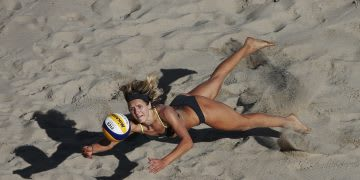 Beach volleyball star Laura Ludwig playing on sand and jumping for a coming ball.
