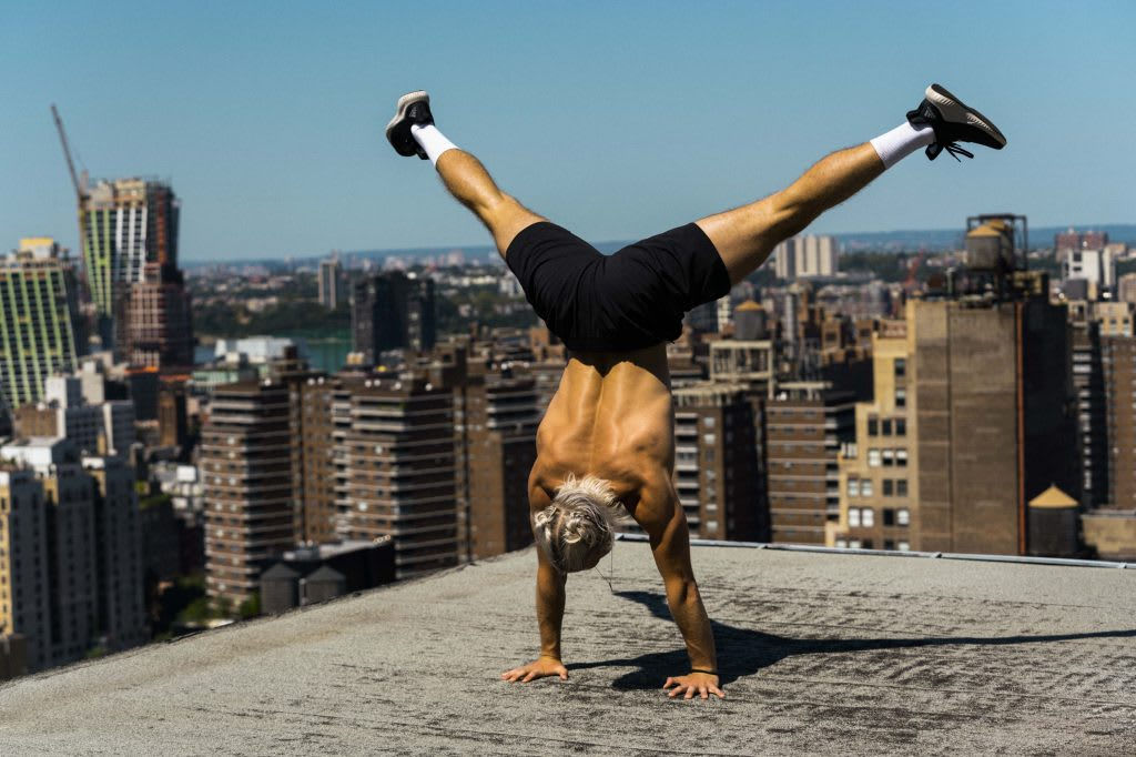 A man doing a handstand on the roof of a house. Fitness, Challenge, Growth Mindset, Mindset, Self-improvement, GamePlan A.